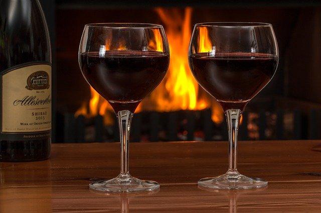 dos copas de vino con una chimenea de fondo